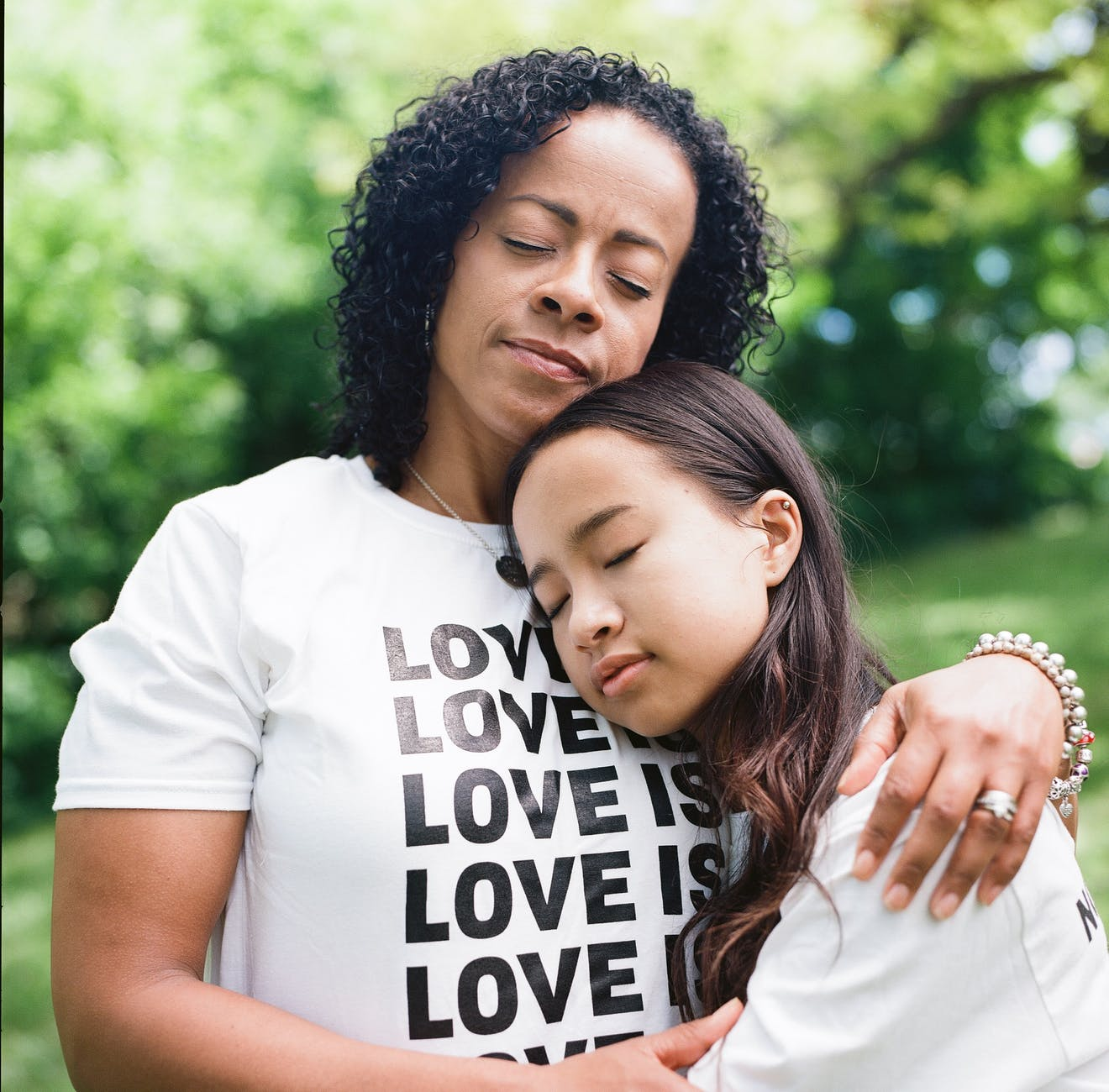 woman in white crew neck t shirt hugging woman shallow focus photography